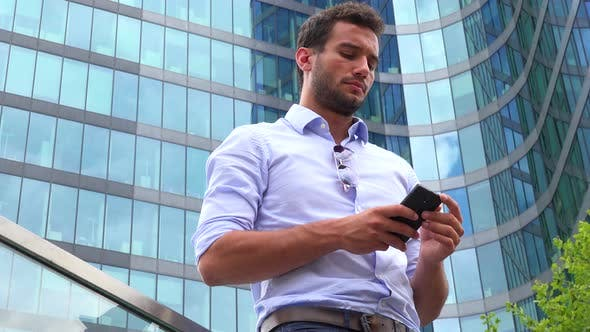 Thumbnail for A Young Handsome Businessman Works on a Smartphone - Closeup From Below - an Office Building