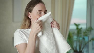 Happy Woman with Laundry in Living Room Taking in That Fresh Laundry Scent