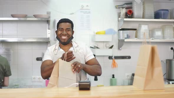 Good-looking Smiling Man Welcomes Customers