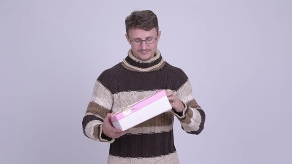 Thumbnail for Happy Bearded Man Thinking While Holding Gift Box