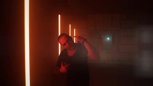 Männlicher Rapper, der nahe rote Lampen geht