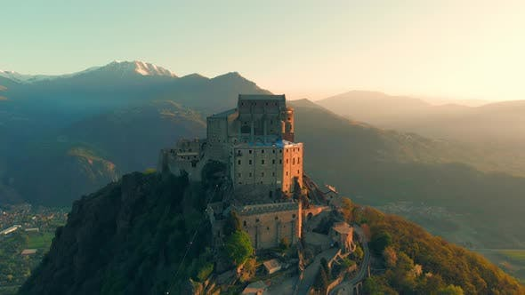 Thumbnail for Drone Flying at Old Medieval Abbey Perched on Mountain Top at Sunrise, Turin Italian Alps