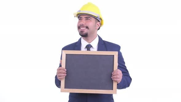 Thumbnail for Happy Bearded Persian Businessman As Engineer Thinking While Holding Blackboard