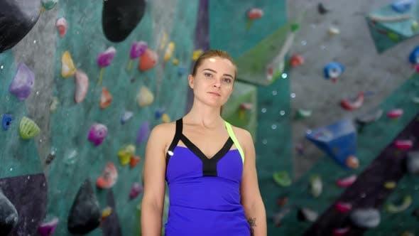 Thumbnail for Female Climbing Enthusiast Posing next to Colorful Walls