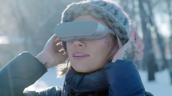 Thumbnail for Girl in Glasses of Virtual Reality Walks Through the Winter Snow-covered Park