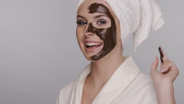 Thumbnail for Happy Woman Applying Facial Clay Mask Isolated on Grey