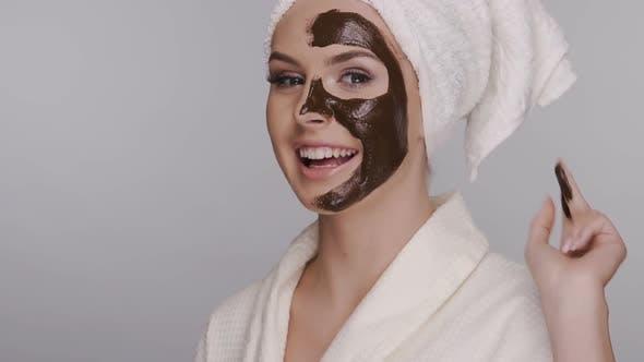 Thumbnail for Happy Woman Anwendung Gesichtsmaske isoliert auf Grau