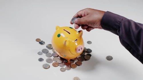Einzahlen von Münzen in Sparschwein
