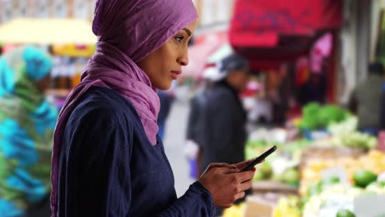 Thumbnail for Beautiful young Muslim woman texting with smartphone outside