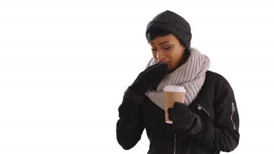 Cute black woman in winter clothes answering text message in studio, smiling