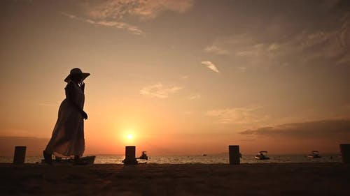 Woman in Large Sun Hat Walking Along Marina Shore
