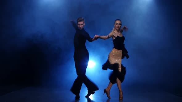 Thumbnail for Happy Couple Dancing Jive in Smoky Studio with Blue Spotlight