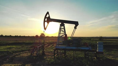 Silhouette Working Oil Pump in Deserted District at Sunset