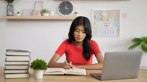 Portrait of Asian schoolgirl studying online making notes in copybook