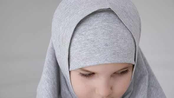 Young Muslim Teen Girl in Hijab Shyly Looking at Camera and Smiling