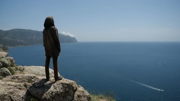 Thumbnail for A Man in a Hood on the Edge of the Cliff in Front of Him Has a View of the Sea