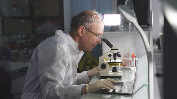Male Scientist or Doctor Specialist Working in Laboratory Analyzing