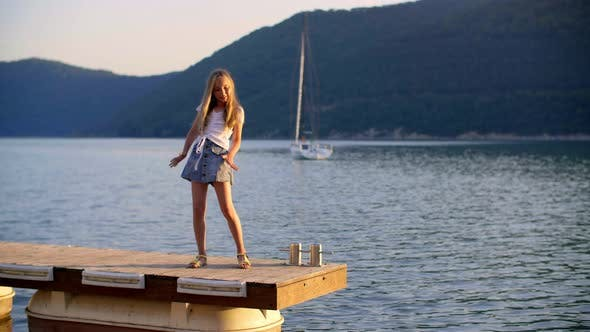 Thumbnail for Happy Teen Girl Dancing on Pier Near Lake Water