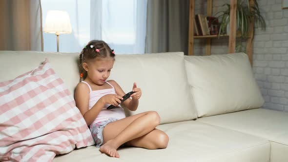 Thumbnail for Little Girl Child Home On Sofa Playing On Smartphone