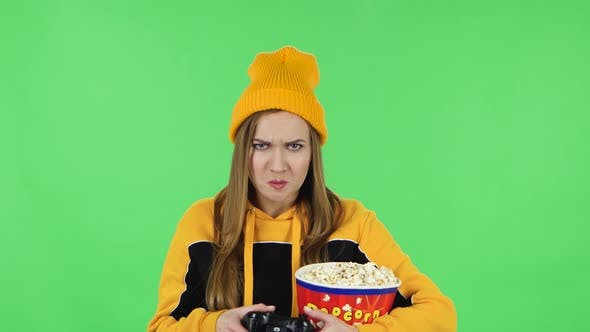 Thumbnail for Portrait of Girl with Popcorn Is Playing a Video Game Using a Wireless Controller and Rejoicing in