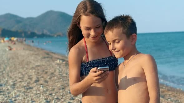 Thumbnail for Children Looking Photo on Smartphone at Sea Beach. Boy with Girl Reviewing Photo
