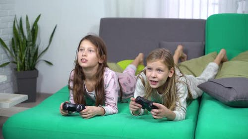 Little Girls Playing Video Games with Game-Pads at Home