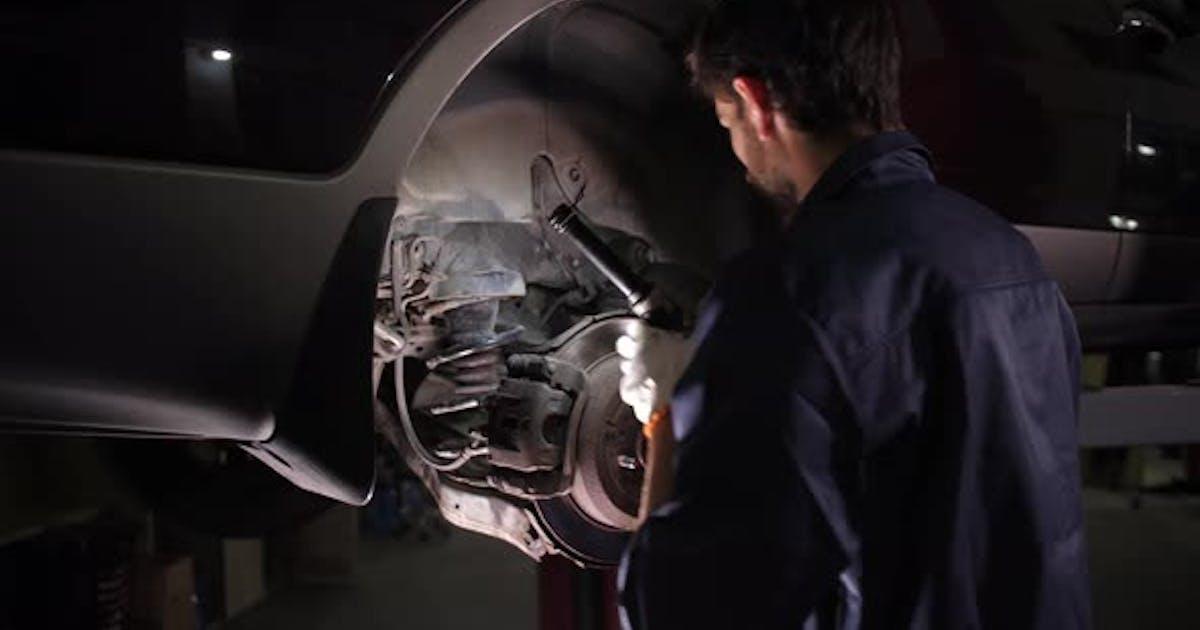 Auto Repair Service Worker Checking Running Gear