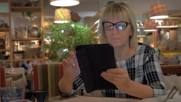 Cover Image for Senior Woman Surfing Internet on Pad in Cafe