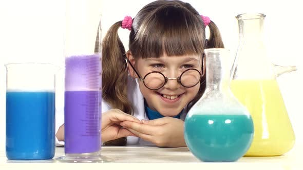 Thumbnail for Cute Little Girl with Two Ponytails in Uniform, Round Glasses Stands Up and Smiling Among Chemical