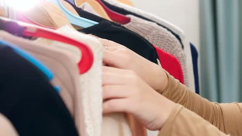 CLoseup of Female Hands Moving Along Clothes Rack in Store and Choosing What To Buy or Wear