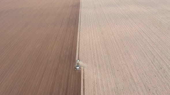Thumbnail for Aerial Shot of a Two Color Agriculture Field with a Tractor Furrowing It in Autumn