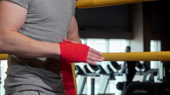 Thumbnail for Cropped Shot of a Male Boxer Applying Wrist Bandages Before Boxing