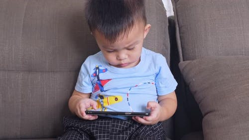 Cute Little Boy Watching Cartoons On Mobile Phone