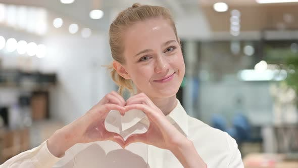Portrait of Loving Young Businesswoman Showing Heart Sign with Hand
