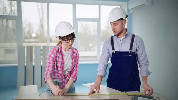 Man and Women in Construction Helmets Make Floor Repairs and Cut Laminate with Tool
