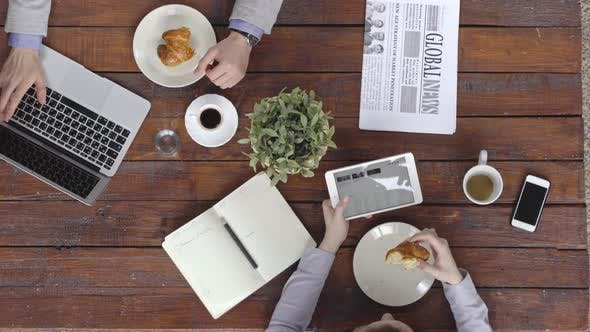 Thumbnail for Business People Using Gadgets at Breakfast