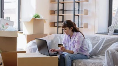Woman with Laptop and Credit Card at New Home