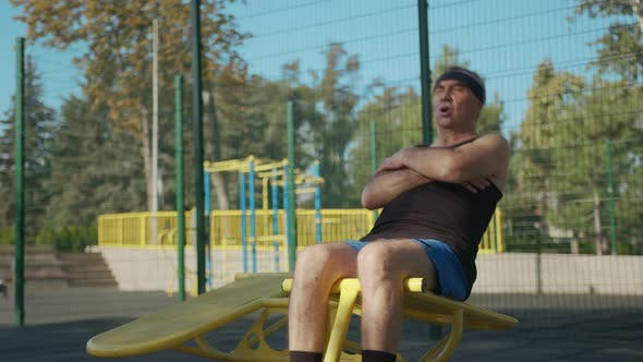 A Retired Elderly Man Works Out on a Sports Ground Outside. Healthy Lifestyle Concept.