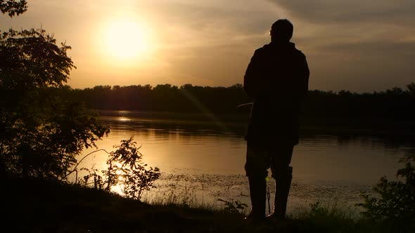 Thumbnail for Fisherman Catches Fish on a Fishing Rod Sunset Beautifully Wraps His Silhouette