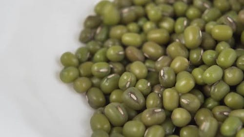 Green Mung beans fall and fill a white ceramic plate.