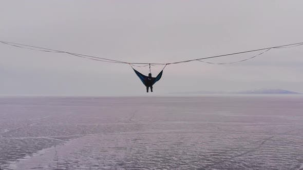 Thumbnail for Silhouette of a Man in a Hammock Mounted at High Altitude