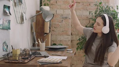 Woman Sitting at Desk and Dancing to Music