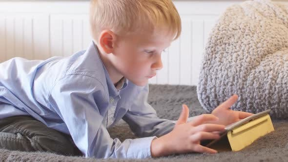 Thumbnail for Little Child Uses Tablet on Sofa at Home