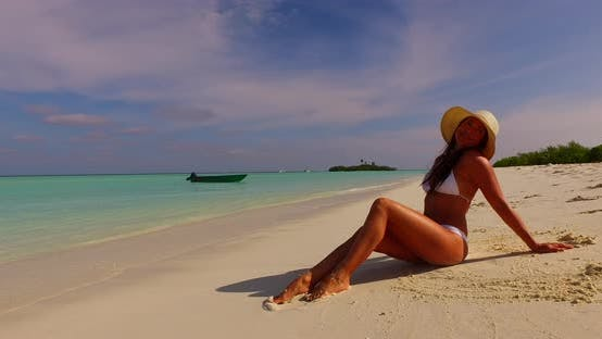 Thumbnail for Modern smiling girl on vacation by the sea on beach on summer white sand and blue background 4K