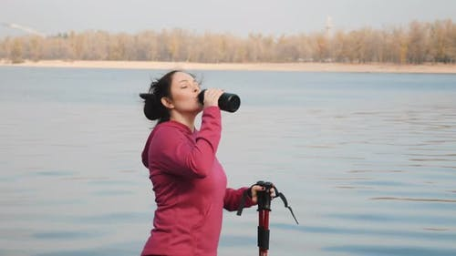 Nordic Walking. Young chubby woman drinking water from bottle