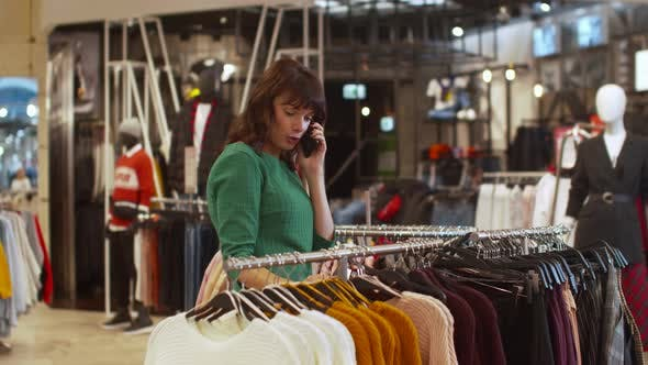 Thumbnail for Nice Woman Choses a Sweater and Talks on the Phone Rapturously