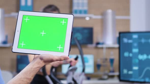 Cover Image for Dolly Shot of Doctor in Sport Science Holding Tablet with Green Screen