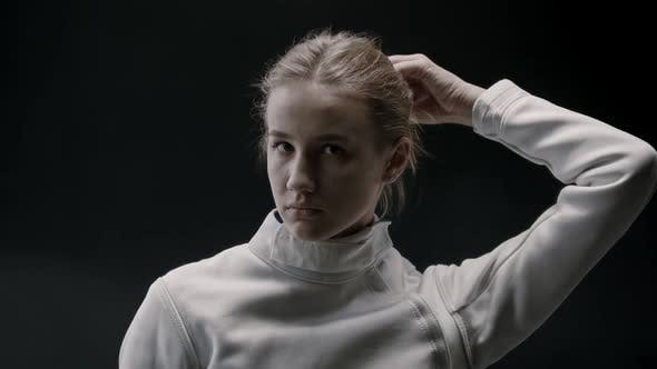 Thumbnail for A Young Pretty Woman Fencer Lets Her Blonde Hair Down and Shakes Her Head