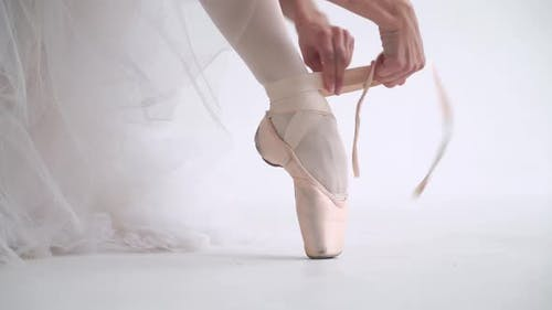 Female in a White Tutu Sits on the Floor and Ties the Ribbons of Her Pointe Shoes, Young Ballerina