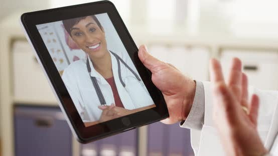 Connected senior doctors talking on tablet